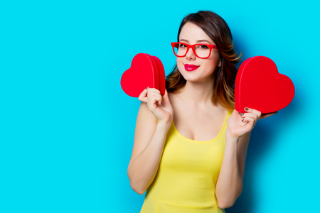 heart shaped: portrait of beautiful young woman with heart shaped gifts on the wonderful blue studio background