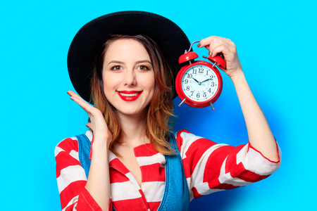 Portrait of young smiling red-haired white european woman in hat and red striped shirt with retro alarm clock on blue background