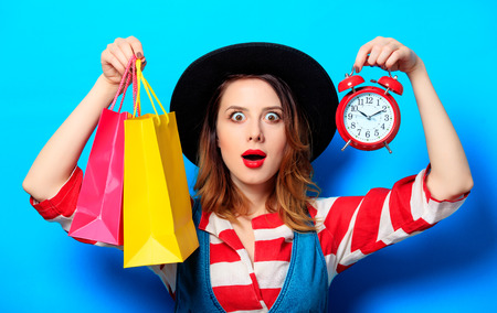 Portrait of young suprised red-haired white european woman in hat and red striped shirt with alarm clock and shopping bags on blue background