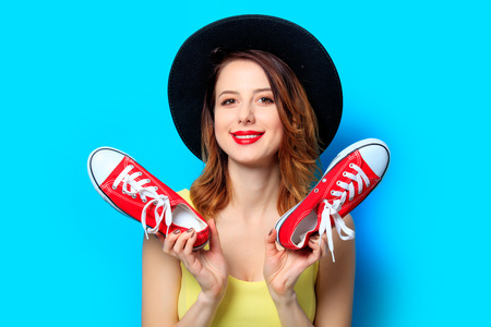 Portrait of young smiling red-haired white european woman in hat with gumshoes on blue background Stock Photo