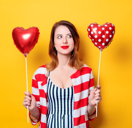 Portrait of beautiful young smiling red-haired white european woman in red striped shirt with heart shape toys on yellow background