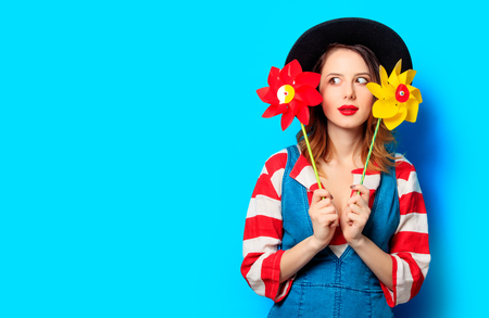 pinwheels: Portrait of young surprised red-haired white european woman in hat and red striped shirt with jeans dress with pinwheels on blue background Stock Photo