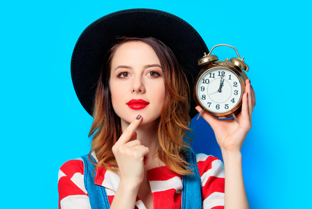 Portrait of young suprised red-haired white european woman in hat and red striped shirt with alarm clock on blue background Stock Photo