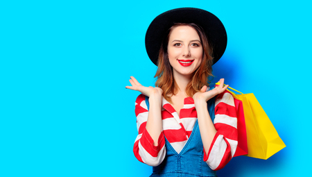 shoppings: Portrait of young smiling red-haired white european woman in hat with colour shoppings bags on blue background