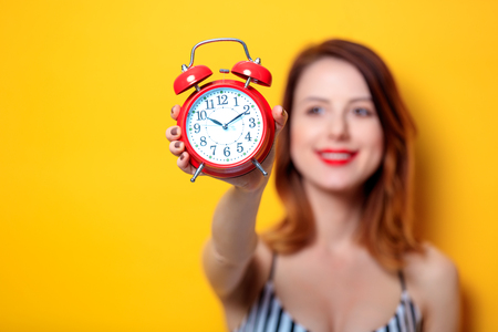 Young red-haired woman holding aged red alarm clock on yellow background
