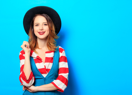 Portrait of young smiling red-haired white european woman in hat and red striped shirt with jeans dress on blue background Фото со стока