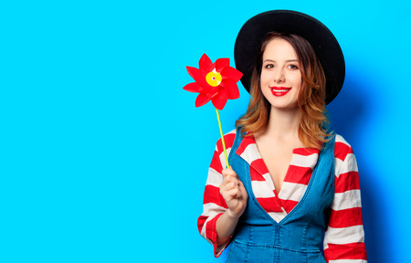 Portrait of young smiling red-haired white european woman in hat and red striped shirt with jeans dress with pinwheel on blue background
