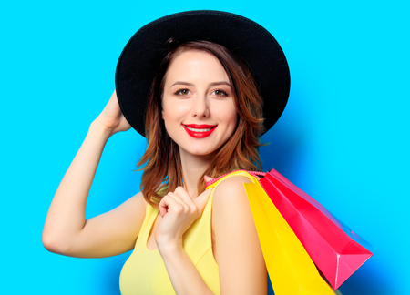Portrait of young smiling red-haired white european woman in hat with shopping bags on blue background