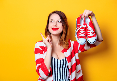 Portrait of beautiful young smiling red-haired white european woman in red striped shirt with gumshoes on yellow background