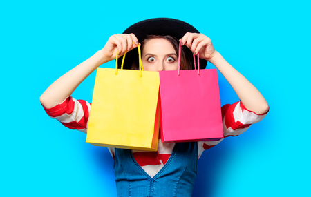 Portrait of young surprised red-haired white european woman in hat with colour shopping bags on blue background