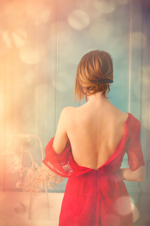 ombre: photo of beautiful young woman standing near bath and taking her dress off. Portrait with bokeh Stock Photo