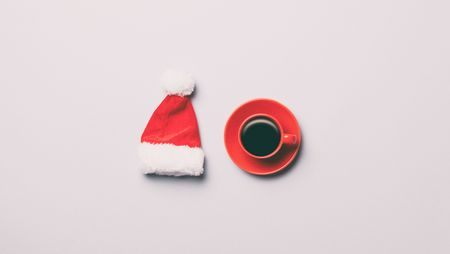 Red Santa Claus hat and cup of coffee on grey background Stock Photo