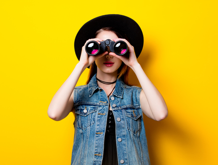 seeking: Portrait of young adult woman in hat with binocular on yellow background