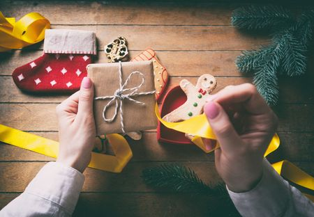 gingerbread man: Young woman hands wrapping christmas gifts and cookies on wooden background, Photo in old color image style