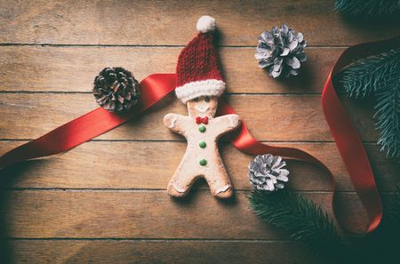 gingerbread man: Hight angle view on ginbgerbread man cookie and Santa Claus hat on wooden background Stock Photo