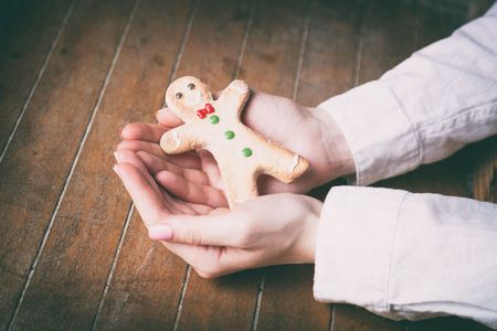 gingerbread man: Young woman hands holding christmas gingerbread man cookie on wooden background, Photo in old color image style