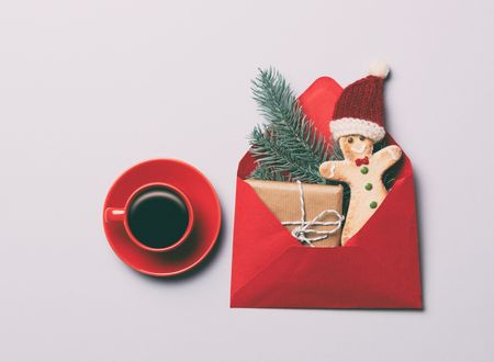 Christmas Red cup of coffee and Gingerbread man cookie with gifts on grey background, view above
