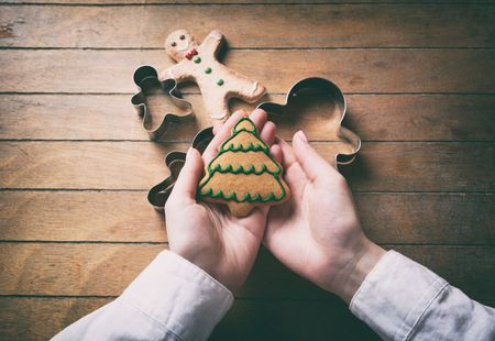 gingerbread man: Young woman hands holding christmas tree cookie on wooden background, Photo in old color image style