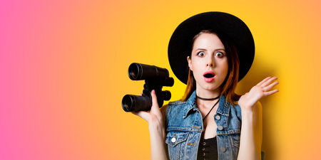 seeking: Portrait of young shocked adult woman in hat with binocular on overflow background