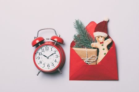 gingerbread man: Red alarm clock and Christmas gifts in envelope on grey background Stock Photo