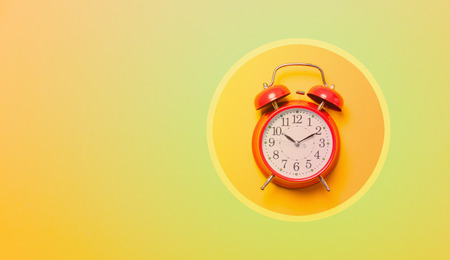 Red alarm clock in cirlce on colored background Stock Photo