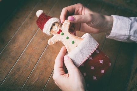 gingerbread man: Young woman hands holding christmas gingerbread man cookie in sock on wooden background, Photo in old color image style