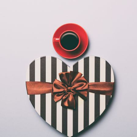Red cup of coffee and heart shape gift on grey background, view above