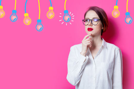 Beautiful puzzled red-haired businesswoman with abstract lamps on pink background