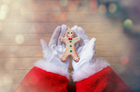gingerbread man: Santa Claus holding Chrstmas cookie on wooden background with bokeh