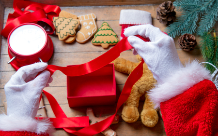 Santa Claus have wrapping a Christmas present box and other gifts on wooden background Stock Photo