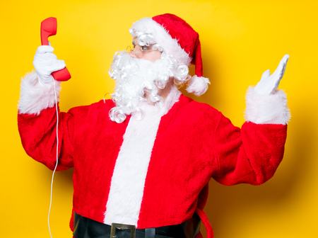 Funny Santa Claus holding red handset on yellow background Stock Photo