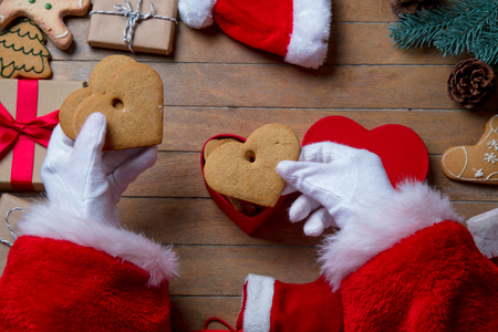 gingerbread man: Santa Claus have wrapping a Christmas cookie and other gifts on wooden background