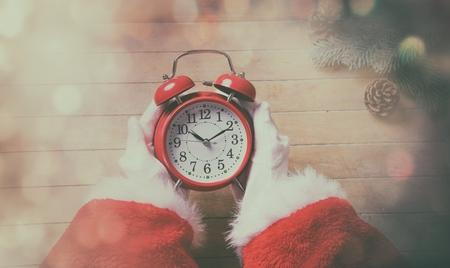 chrstmas: Santa Claus holding Chrstmas alarm clock on wooden background with bokeh Stock Photo