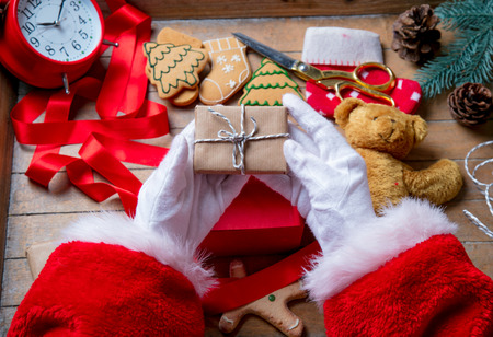 gingerbread man: Santa Claus have wrapping a Christmas present box and other gifts on wooden background Stock Photo