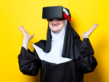 Young happy nun with Virtual Reality Glasses on yellow background