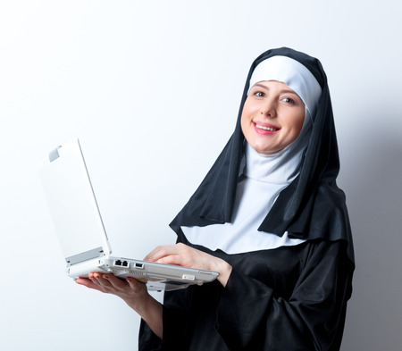 Young smiling nun with laptop computer on white background