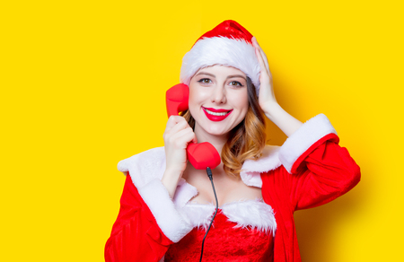 Portrait of Young Santa Clous girl in red clothes with handset on yellow background Stok Fotoğraf - 81491844