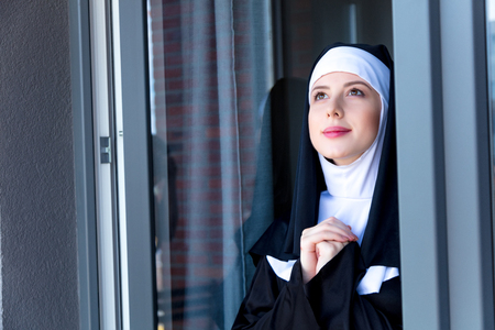 Young smiling nun near window reflection in house