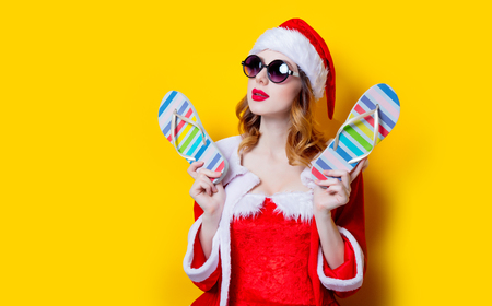 Portrait of Young Santa Clous girl in red clothes with sunglasses and flip flops on yellow background