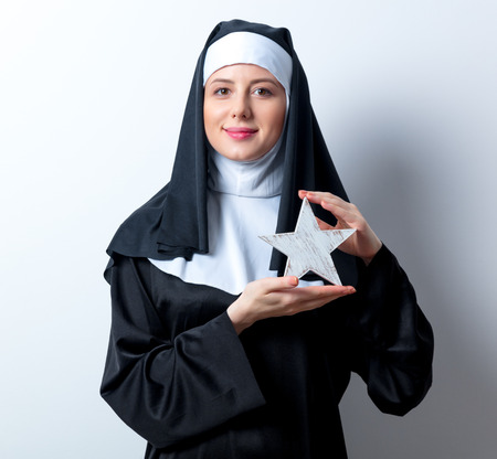 sotana: Young smiling nun with star shape on white background