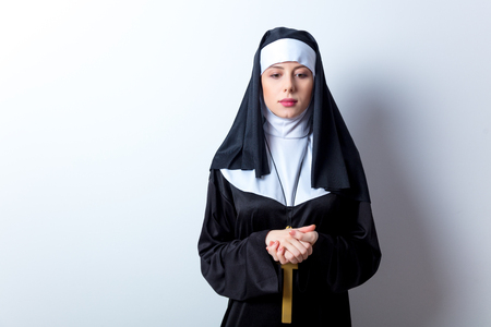 Young serious nun with cross on white background