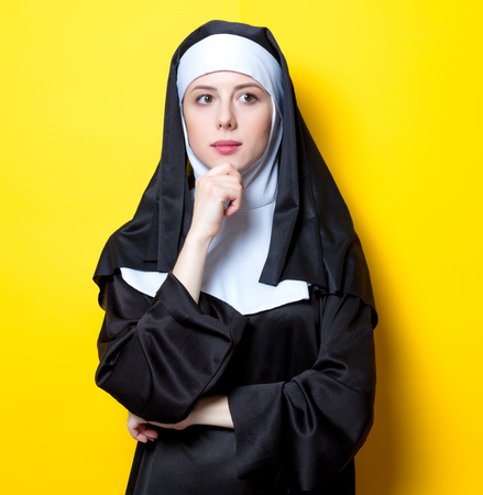 Young serious nun on yellow background