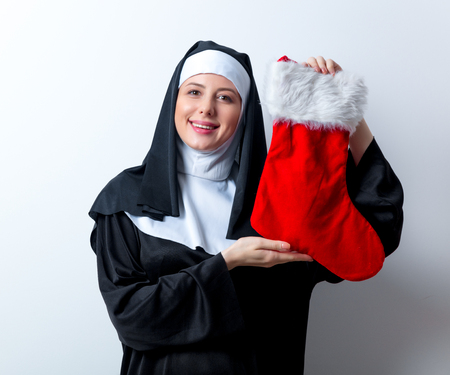 Young smiling nun with Christmas sock on white background