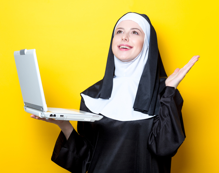 Young smiling nun with white laptop computer on yellow background Stock Photo