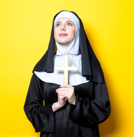 Young serious nun with cross on yellow background Stock Photo