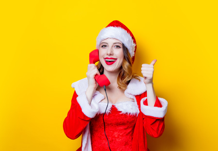 Portrait of Young Santa Clous girl in red clothes with handset on yellow background Stok Fotoğraf - 81273806