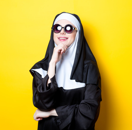 Young happy nun with sunglasses on yellow background Stock Photo