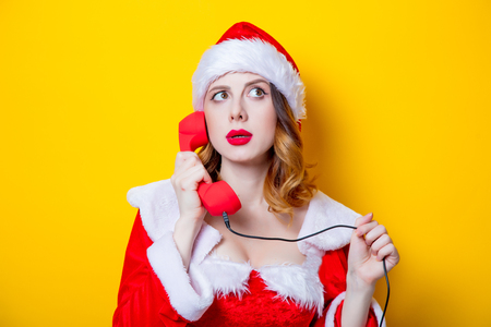Portrait of Young Santa Clous girl in red clothes with handset on yellow background Stok Fotoğraf - 81491853