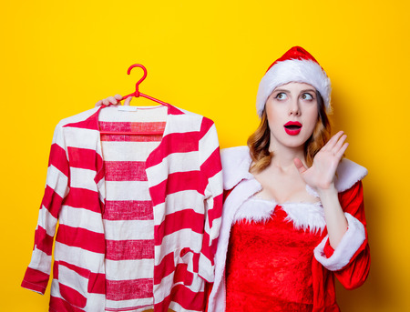 choise: Portrait of Young Santa Clous girl in red clothes with shirt on yellow background