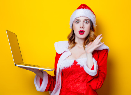 Portrait of Young Santa Clous girl in red clothes with laptop computer on yellow background